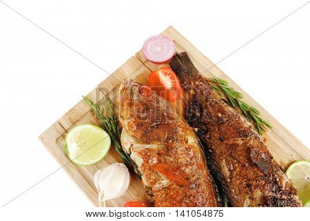 savory on wood: two fried fish served with tomatoes and lemon