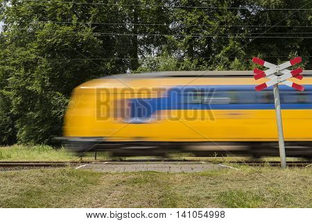 Dutch train passing by on a railway crossing near Ellecom in the Netherlands