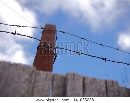 Steel barb wire on a fence under cloudy sky Australia 2016