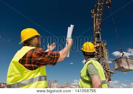 Construction workers signaling to crane operator, horizontal