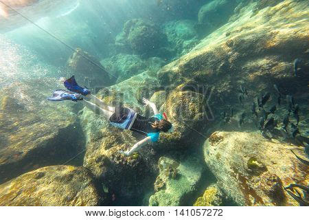 Man apnea swims in deep waters of the popular Similan Islands in Thailand, Andaman Sea.