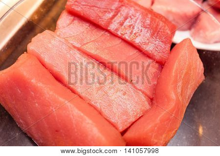 briquettes of fresh tuna meat on metallic platter
