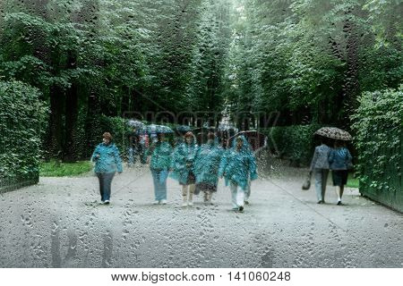 people in raincoats in the blur in the Park in the rain
