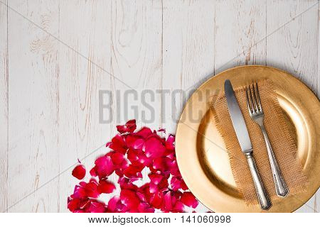 Silverware With An Empty Tag On A Table With At Gold Plated And Rose Petals