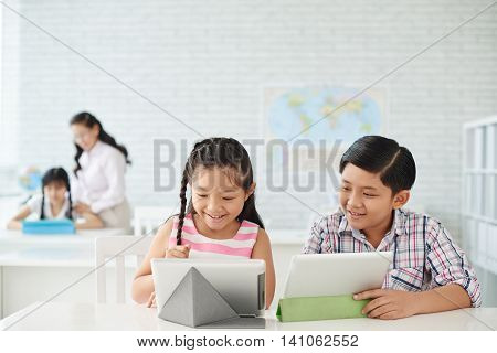 Little classmates using applications on tablet computers