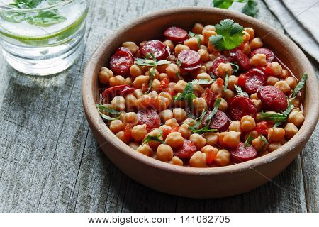 Chickpeas with chorizo in a clay bowl on the table close-up