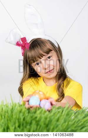 Beautiful little girl dressed in bunny ears is holding  Easter eggs on a gray background