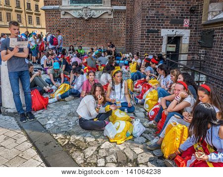 KRAKOW POLAND - JULY 29 2016:. World Youth Day 2016. Young pilgrims from various countries sitting on the ground resting eating and talking in groups in the shadow of st Mary church at the Market Square in Cracow.