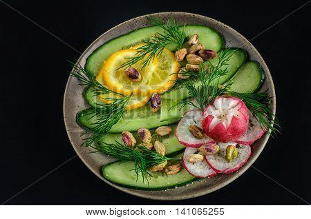 Cutting of vegetables on a ceramic plate of cucumber radish lemon with pripravali