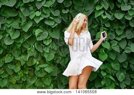Dancing blonde girl with listening to music on a smartphone outdoor. Happy young woman enjoy sunset while dancing and enjoy music on headphones.