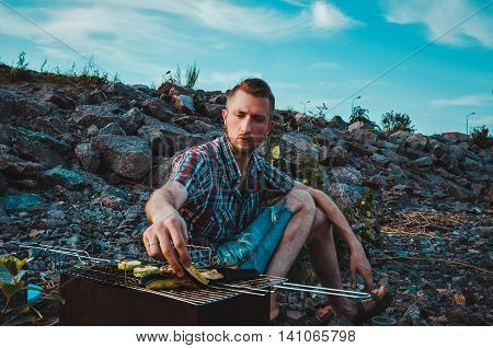 Serious young man cooking vegetables on the barbecue rack with a pair of tongs outdoor food items set. Bearded male sitting on rocky beach Baltic seaside. Summer BBQ and grill tools concept. Outdoor lifestyle portrait.