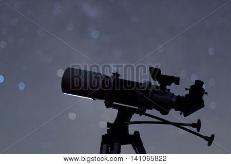 Silhouette of Telescope in real night sky. Blurred night sky. Blurred milky way. Refractor type telescope