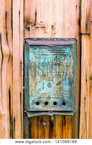 Old blue mailbox with rust and a hole and dirty mail on a wooden wall. Close up