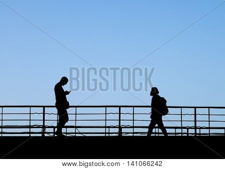 Silhouettes of two people walking towards each other by footbridge. One holds smart phone other with backpack listening to music through headphones.