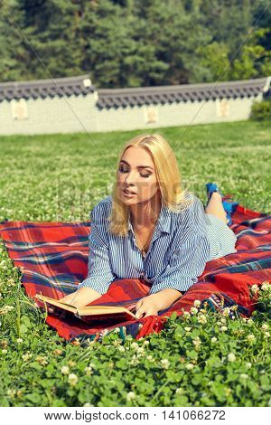 Beautiful smiling woman lying on a grass outdoor. Absolutely happy blonde girl rest in the green park at summer. Woman relaxing with a book.