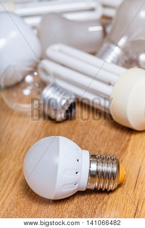 new LED lamp and pile of old incandescent light bulbs and used compact Fluorescent lamps on wooden board
