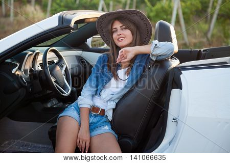 Cowboy girl driver sits in white cabriolet