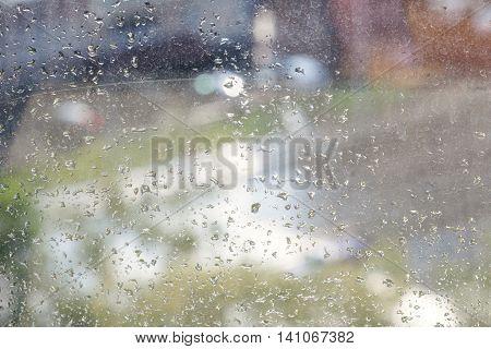 Raindrops On Windowpane And Blurred Urban Street