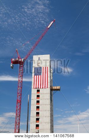 BOSTON, MASSACHUSETTS,USA - JULY 15,2016: New construction luxury condos on Fan Pier in Boston. Huge American flag adorns buildings under construction along Harborwalk in South Boston