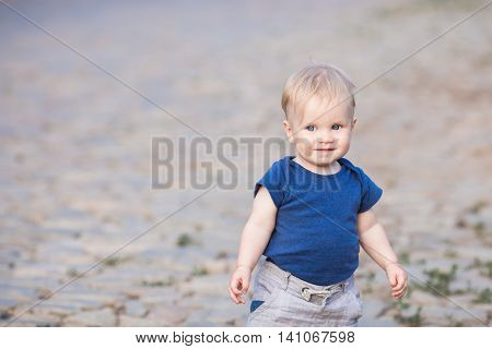 Happy cute boy on old roadway. Smiling one child outdoors on Road paved with stone on the sunset
