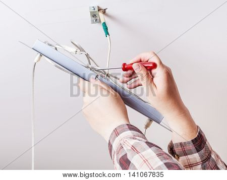 Electrician Repairs Wiring In Ceiling Lamp