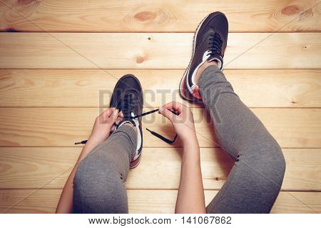 Girl tying shoelaces sitting on the wooden floor. top view