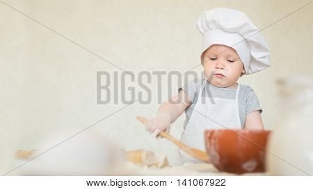 Portrait of the little boy in a suit of the cook sculpts dough. Baby make dinner in chef suit. Cooking concept with free text space - copy space