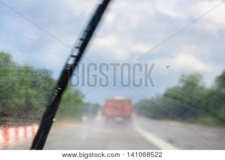 wiping windscreen during driving car on highway in rain (focus on glass)
