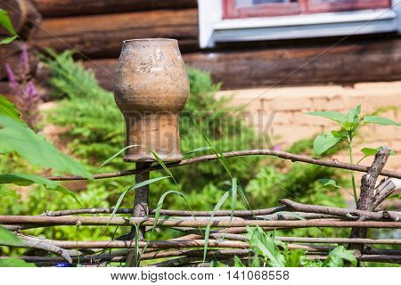 Wattle Fence With Old Clay Pot And Log House