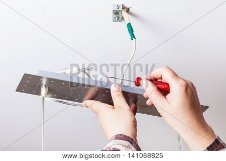 Electrician Fixes Wiring In Ceiling Lamp