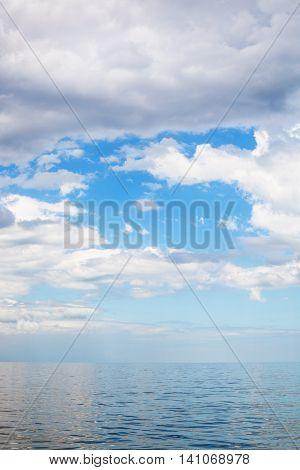 Cumulus Clouds Over Calm Blue Water Sea Of Azov