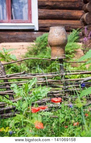 Wattle Fence With Clay Pot And Old Cottage