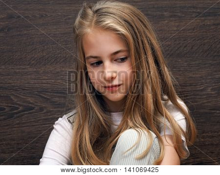 Portrait of a teen girl. Long blond hair a pretty face. Background dark wooden board. The child thought dreams