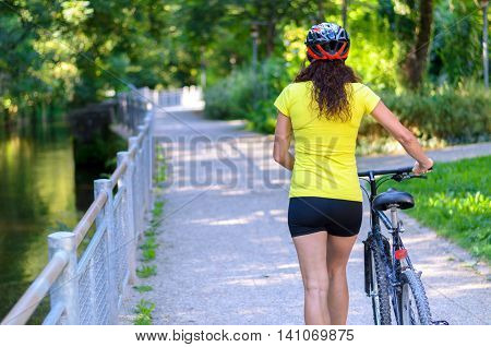 Fit Muscular Woman Wheeling Her Bicycle Outdoors