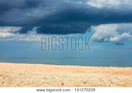 Landscape With Sand Beach And Rain Clouds Over Sea