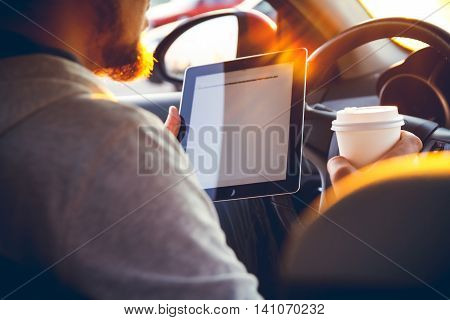 A young man with a tablet in his hand at the wheel of the car. Multitasking. Safe driving concep