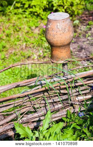 rural scenery - wattle hurdle with old clay pot