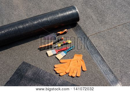 Roll waterproofing brush wire brush trowel knife gloves. Tool for waterproofing on a background of flat roof.