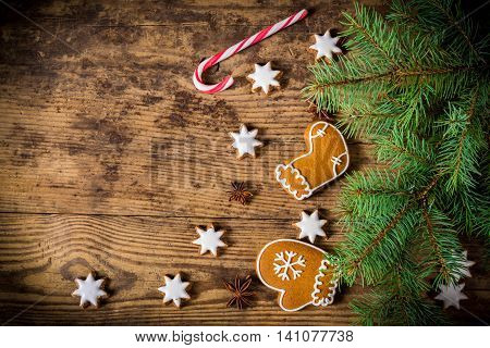 Old wooden christmas background with gingerbread cookies and tree, empty space for text