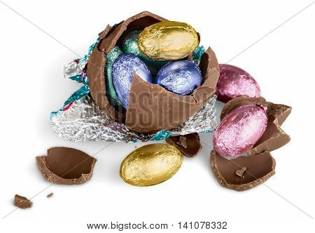 Broken chocolate Easter egg wrapped in pink foil with colorful candies on white background