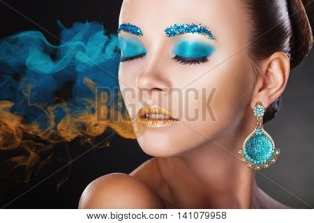 Young woman with fashion colorful makeup with multi-colored smoke