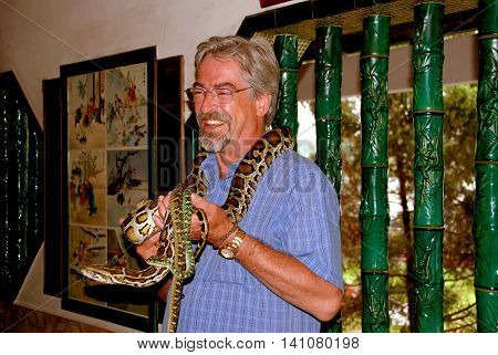 Penang Malaysia - January 10 2008: Visitor to the mysterious 1851 Chinese Snake Temple poses with several of the resident viper snakes wrapped around his neck and arms
