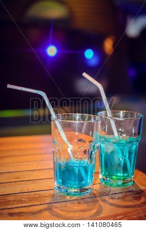 Blue cocktail on bar background. Blue cocktail with blue curacao liqueur. Blue Soda on a wooden table. Alcoholic and Non-alcoholic drink.