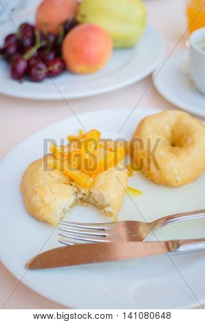 Breakfast including donuts with candied orange jam coffee orange juice and fruits. Healthy breakfast. Good morning. Breakfast table. Morning breakfast with classic donuts and honey.