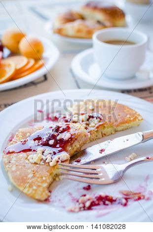 Breakfast table including pancakes with raspberry jam, coffee, pastries and fruits. Healthy breakfast. Good morning. Morning breakfast with classic pancakes and jam. Selective focus.
