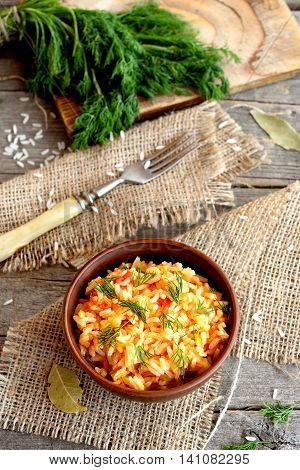 Risotto with vegetables in an earthenware bowl, fork, dill sprigs, a kitchen board on a wooden background. Rice with tomatoes, garlic, carrots and dill. Popular way of cooking rice in Italy. Top view
