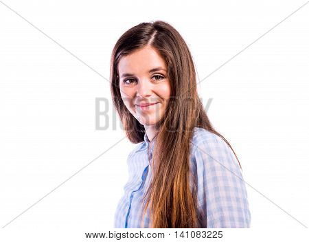 Teenage girl in blue checked shirt, smiling. Young beautiful woman, studio shot on white background, isolated