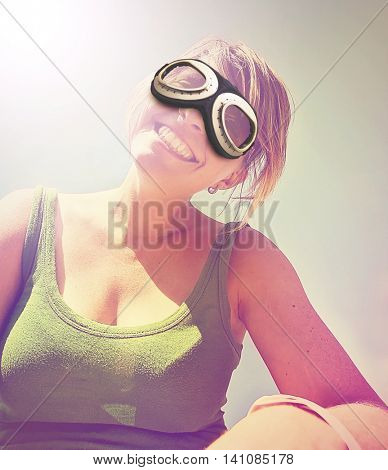 a cute girl smiling at the camera on a bright sunny day with pilot goggles on toned with a retro vintage instagram filter