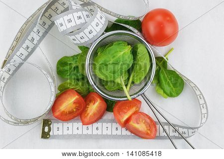 Strainer with spinach, tomato and centimeter on white background