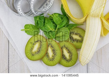 The Ingredients spinach, kiwi and banana for a tasty smoothie and a centimeter to measure the results of a diet.